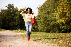 Young woman in fashion blue jeans and red bag walking in autumn Stock Photo