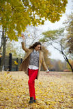 Young woman in fashion coat walking in autumn park Royalty Free Stock Photo