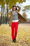 Young woman in fashion coat walking in autumn park Stock Photography