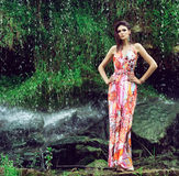 Young woman in a fashion dress posing next to a waterafll Stock Photos