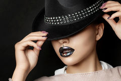Young woman with fashion make up straightens her hat Stock Photos