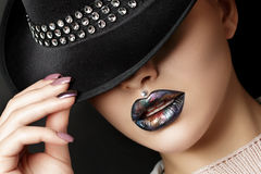Young woman with fashion make up straightens her hat Royalty Free Stock Photos