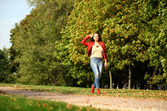 Young woman in fashion red jacket and blue jeans walking in autu stock images