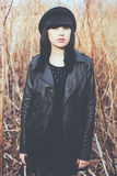 Young woman is posing in fashionable hat and leather jacket. Outdoor portrait. Portrait of the girl in a dark clothes Royalty Free Stock Images