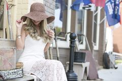 Young woman with fashionable hat. Young woman sitting on bench in city street wearing fashionable flouncy hat Royalty Free Stock Image