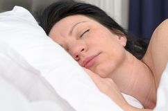 Young woman fast asleep in her bed. In a low angle view over a clean white pillow of her face Stock Photography