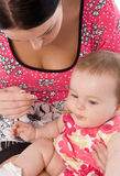 Young woman feeding her baby daughter Royalty Free Stock Photography