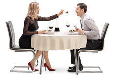 Young woman feeding her boyfriend salad at restaurant table Stock Photo