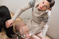 Young woman feeding her cat at home Royalty Free Stock Photo