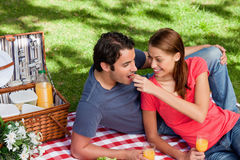 Young woman feeding her friend as they as they lie on a blanket Stock Photography