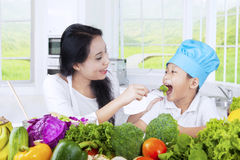 Young woman feeding her kid with vegetables Stock Photos