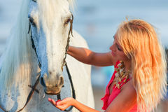 Young woman feeding a horse Royalty Free Stock Photo