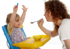 Young woman feeding little girl Royalty Free Stock Photos