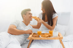 Young woman feeding man in bed Stock Images