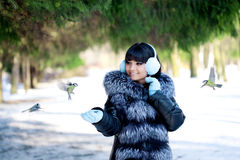 Young woman feeding winter birds Royalty Free Stock Images
