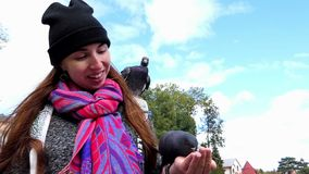 A young woman feeds doves from her hands in slo-mo. A young woman smiles happily and feeds grey doves from her hands in slow motion. She stands on a sunny square stock video footage