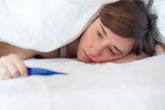Young woman feeling anxious after pregnancy test. Sad woman waiting pregnancy test result stock photo