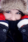 Young woman feeling cold. Young pretty woman hiding her face from the cold on a winter day outdoors Royalty Free Stock Photo