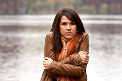Young woman feeling cold. Young woman inbrown leather jacket feeling cold near the lake during a late autumn day. Selective focus on model Stock Image