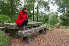 Young woman feeling depressed sitting on a forest Stock Photography
