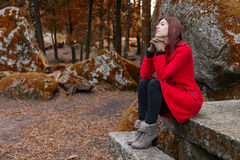 Young woman feeling depressed sitting on a stone table Stock Photography