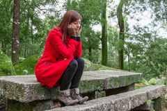 Young woman feeling depressed sitting on a stone table Royalty Free Stock Photo