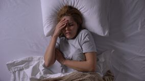 Young woman feeling fever and ache in bones, catching virus and lying in bed. Stock footage stock footage
