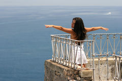 Young woman feeling free. Beautiful girl on balcony feeling free like a flying bird and raising arms Stock Images