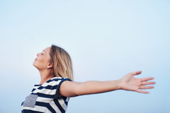 Young woman feeling free under a blue sky Royalty Free Stock Image