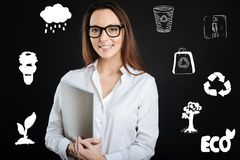 Young woman feeling glad while being ecofriendly and helping nature. Eco friendly. Cheerful young clever volunteer feeling happy and smiling while leading a royalty free stock image