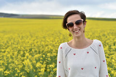 Young woman feeling happy in the middle of a canola field Royalty Free Stock Image