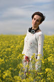 Young woman feeling happy in the middle of a canola field Royalty Free Stock Photos
