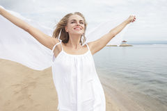 Young woman feeling happy with white scarf. Portrait of young woman feeling happy with white scarf on the beach Royalty Free Stock Photography