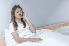 Young woman feeling headache and discomfort on white bed in her bedroom. Young asian woman feeling headache and discomfort on white bed in her bedroom stock image