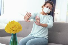 Young woman feeling hypersensitive to spring flowers. Impossible scent. Young curly woman feeling unwell experiencing hypersensitivity to freshly-bloomed spring Stock Photos