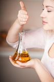 Young woman feeling oil flavor from jug. Close up photo of young woman feeling oil flavor from jug. Concept for cooking in the kitchen Royalty Free Stock Photography