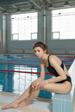 Young woman feeling pain in her foot at swimming pool. Sports exercising injury.  Stock Images
