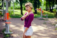 Young woman feeling pain in her shoulder, neck during sport work. Young woman feeling pain in her shoulder during sport workout in the park. Sport, medicine and royalty free stock photo