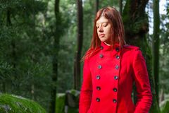 Young woman feeling sad walking alone on forest path wearing red long coat. Or overcoat. Girl passes track on walk in woods of nature park during fall, autumn Stock Photo