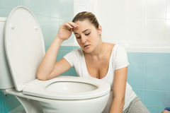 Young woman feeling sick and leaning on toilet Royalty Free Stock Image