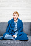 Young woman feeling sick or sad wrapped in cozy blue blanket and sitting on sofa at home. Staring Blankly Ahead Stock Photos