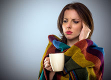 Young woman feeling unwell. Rubbing her temple with her hand with a troubled expression as she stands wrapped in a blanket with a cup of coffee, with copy space Stock Photo