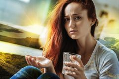 Young woman feeling unwell while sitting with pills and water. Frustrated woman. Tired ill young woman looking upset while sitting with a glass of water and Royalty Free Stock Images