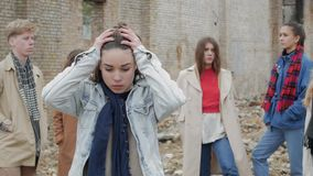 Young woman feels grief. A young woman feels grief among a group of young people in the ruins. The youth makes a theater etude amid a collapsed brick building stock video