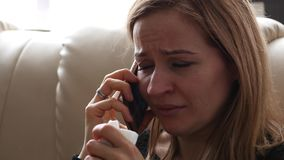 Young woman feels sad and crying while speaking with someone on smartphone. 4K. Young woman feels sad and crying while speaking with someone on cellphone stock video footage