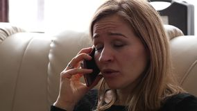 Young woman feels sad and crying while speaking with someone on smartphone. slow motion. Young woman feels sad and crying while speaking with someone on stock video footage