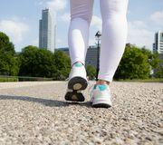Young woman feet walking in city park Stock Photos