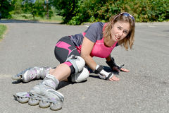 Young woman fell on skates Royalty Free Stock Photography