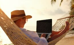 Free Young Woman Female Freelancer Using Laptop While Lying In Hammock On The Tropical Beach At Sunset Stock Photo - 219756970