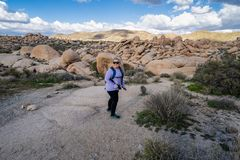 Young woman female hiker wearing a backpack starts off on a hiking trail in Joshua Tree National Park, to the Arch Rock stock photos